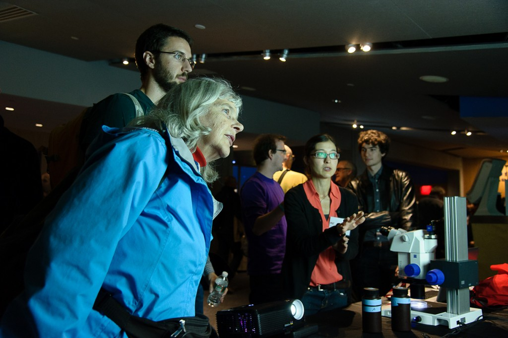 Darcy Taniguchi discusses marine microbes as guests look on at the diminutive creatures darting across the screen. Credit: John Gillooly