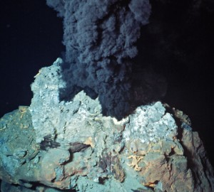 A black smoker chimney releases hydrothermal vent fluid. (Courtesy of WHOI Archives)