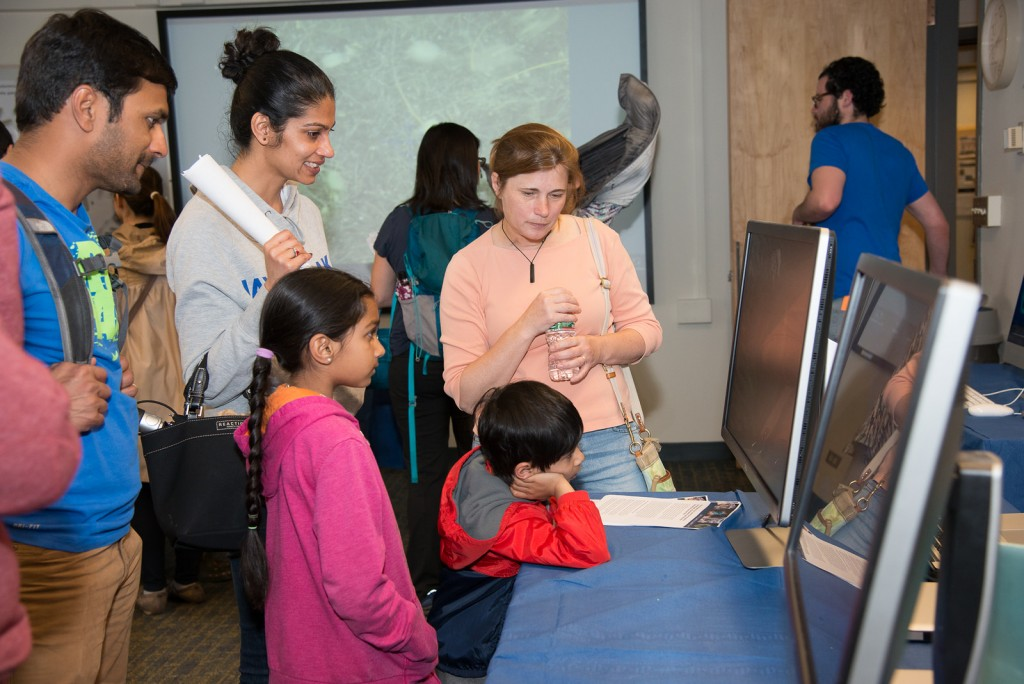 A family watches videos of global ocean currents and chlorophyll from phytoplankton as EAPS Research Scientist Stephanie Dutkiewicz explains (Image: Vicki S McKenna)
