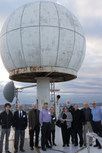 MIT friends, faculty and Austin family pose in front of a radome Polly helped install at MIT.