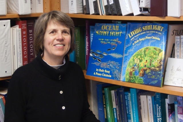 "Institute Professor Sallie (Penny) Chisholm poses with the first two books in the ""Sunlight Series,"" a collection of children's books that teach Earth's natural processes from the point of view of the sun. The latest book in the series is ""Rivers of Sunlight: How the sun moves water around the Earth."" (Photo courtesy of Penny Chisholm)"