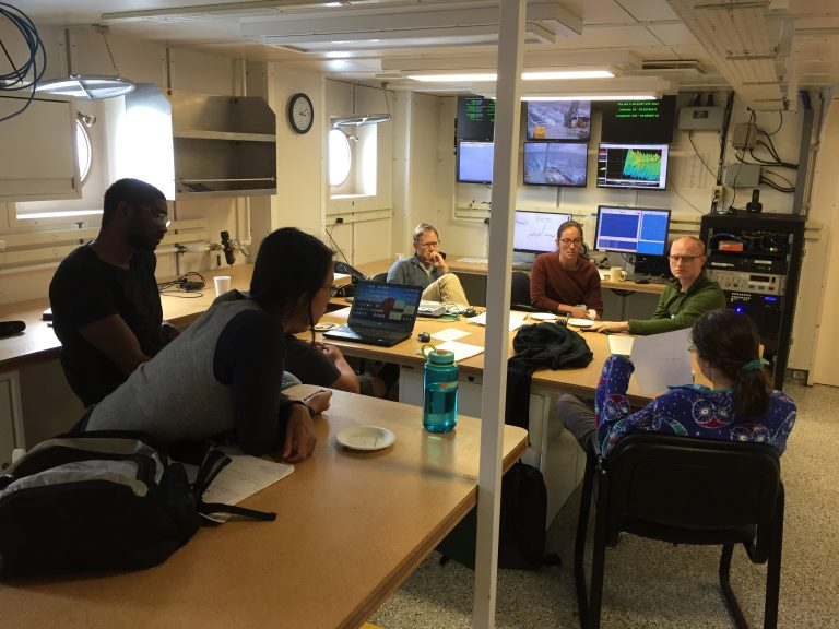 The science party gathered in the main lab, discussing gravimeter data. (Photo by J.-A. Olive.)