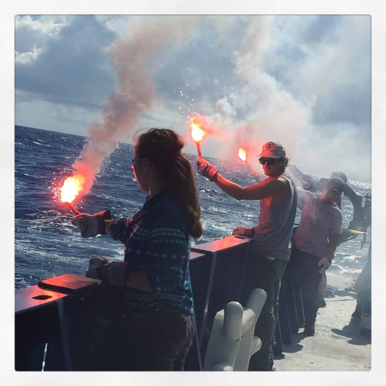 Students and crew members practice using handheld distress flares.  (Photo by J.-A. Olive.)